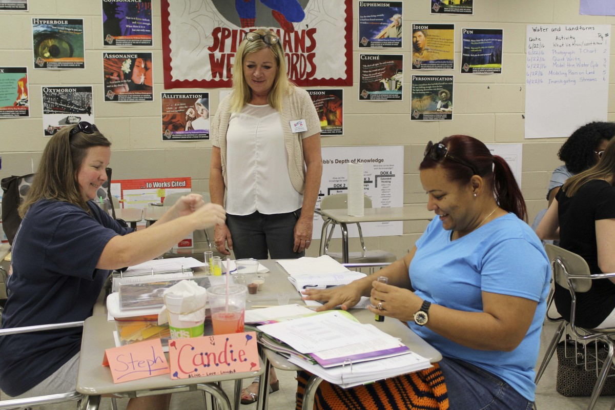 Several Butler County teachers attended AMSTI training last week to learn new Science standards. Stephanie Wattford, fourth grade teacher at McKenzie, left and Candace Powell, fourth grade teacher at Georgiana, work on an activity with the assistance from AMSTI-specialist Tina Kanaley, center. (Photo by Tori J. Norris)