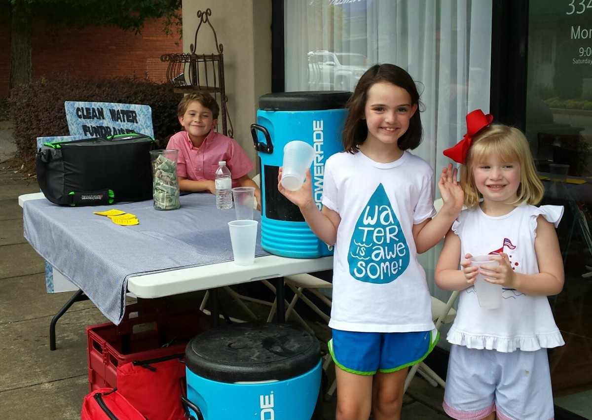 From left, Sam Judah McLendon, Wynn Lowery and Ann Knox McLendon set up a lemonade and water stand to raise money for clean water in underdeveloped countries. (Mollie S. Waters | The Standard)