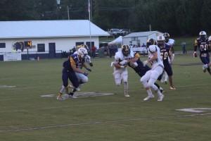 Tigers quarterback Daniel Gaston pushes off a defender as he runs the ball. (Photo by Tori J. Norris)