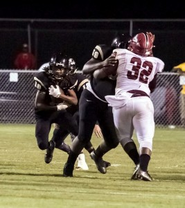 Running back Jamarcus Jones runs up the middle and gets a block from GHS center Trevarn Caldwell. (Cecil Folds/The Standard)