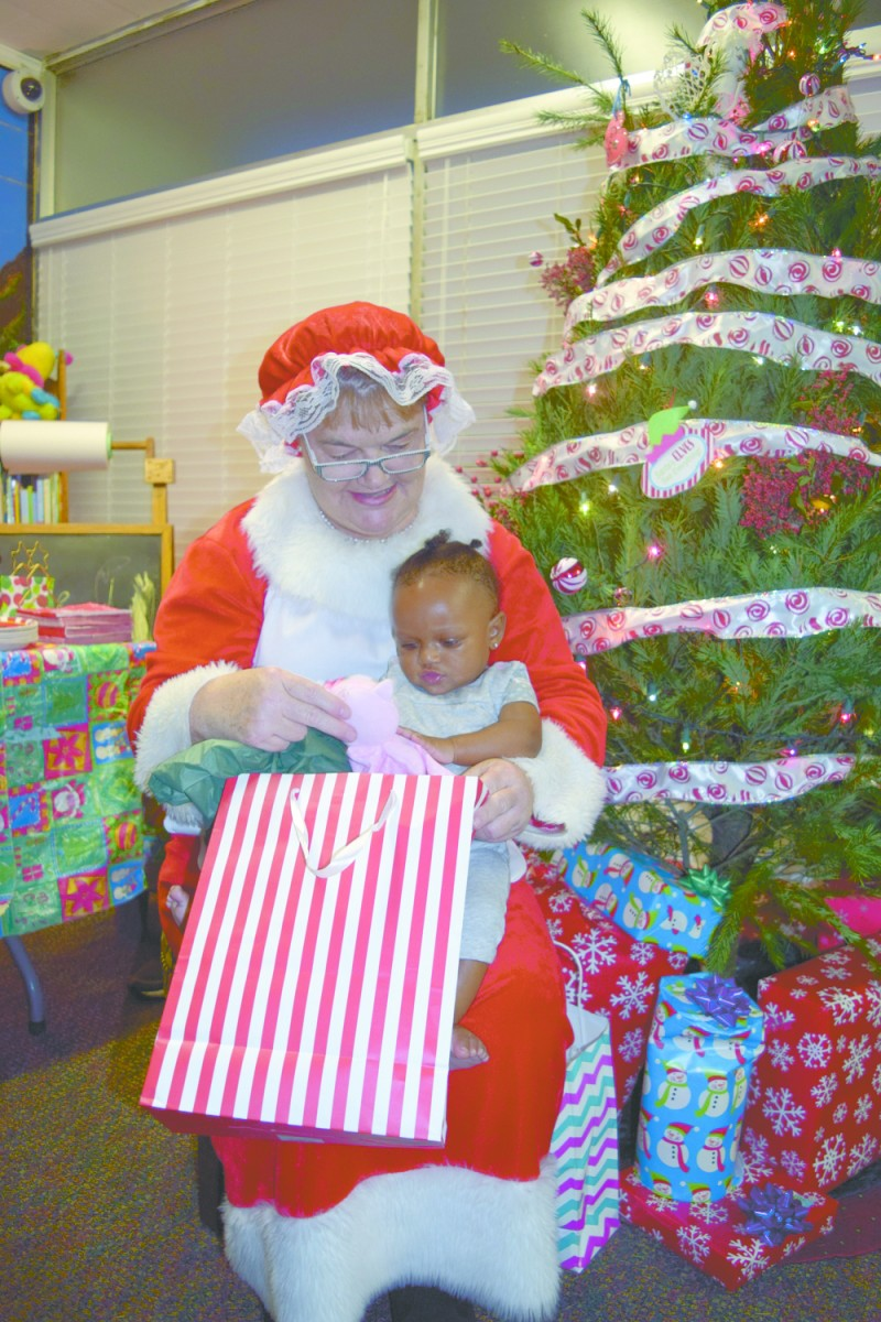 Mrs. Claus, Joanne Mathews, has Kamryn Mallory sitting in her lap receiving a Christmas gift donated by the Greenville Kiwanis Club. In coordination with Safe Harbor, Kiwanis buys gifts for 10 needy families in the greater Greenville Area. In addition, they fed each family as they came by to pick up their gifts. The program has been an ongoing event for many years. Kiwanians and Key Clubbers go Christmas shopping for gifts approximately a week before and they wrap one present to give to each of the children of the families. The wrapped presents are then given out to the children of the families when they come by. All the extra presents are hidden from the children and loaded into the families' vehicles to be take home for Christmas Day. (Bruce Branum | The Standard)